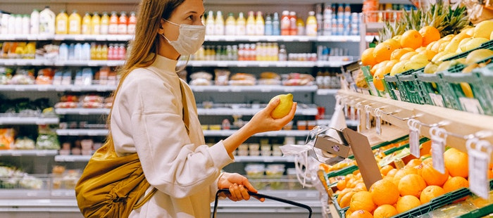 woman with a face mask holding lemon in a supermarket